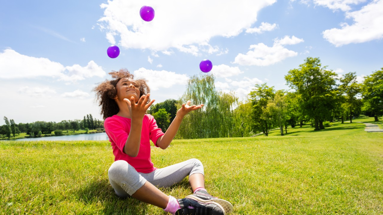 Girl juggling in a park