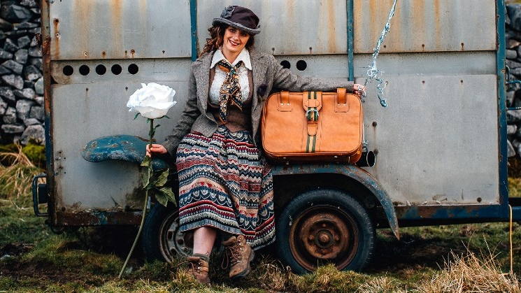 Elsie with big flower and suitcase by tractor